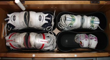 Shoes in bench with wastebaskets