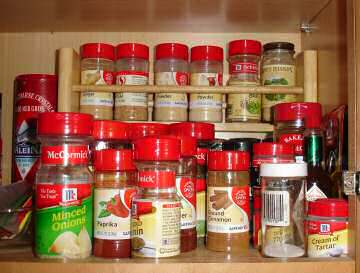 Before photo of spices in kitchen cabinet